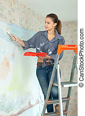 girl paints wall with brush