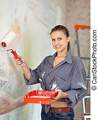 girl paints wall with roller