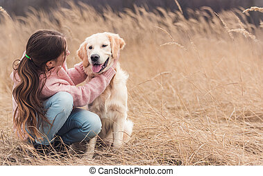 Happy girl petting young dog
