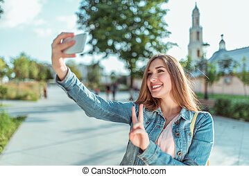 Happy girl pictures herself on phone, selfie on smartphone, denim jacket, summer in city park. Emotions of happiness, joys fun relaxation. Record video messages, online call in Internet application.