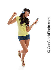 A happy vivacious girl playing music on a portable player and dancing