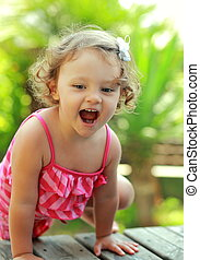 Happy girl playing on summer green background outdoor