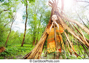 Happy girl playing Red Indian in the forest