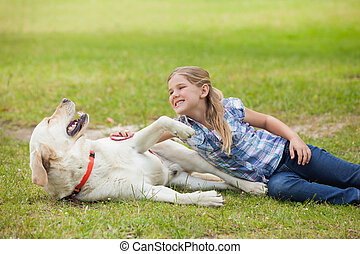 Happy girl playing with pet dog at park