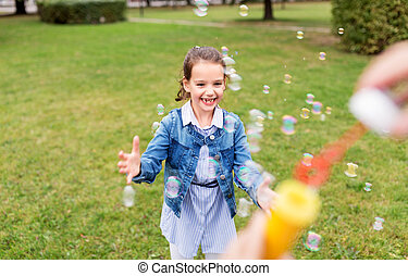 happy girl playing with soap bubbles at park
