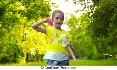 Happy girl playing with soap bubbles in summer park - Happy...