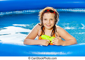 Happy girl playing with water gun in the pool