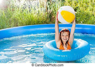 Happy girl playing with wind ball in the pool