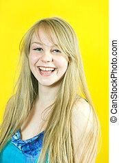 Portrait of happy girl over yellow background