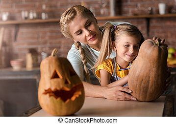 Happy girl preparing a pumpkin for Halloween with her mother
