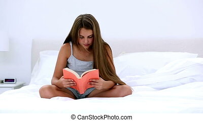 Happy girl reading a book on bed at home in bedroom