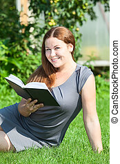 Happy girl reading a book, sitting on green grass