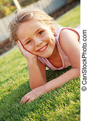 Happy girl relaxing on a grass