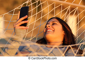 Happy girl resting on a hammock using a smart phone