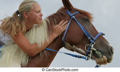 Happy girl rider in saddle hugging and stroking her horse...