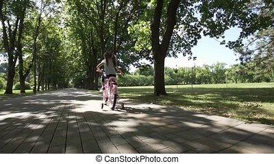 Happy girl riding bike in the park