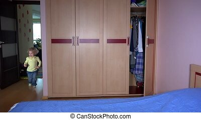 Happy girl run and hide in bedroom wardrobe. Mother find her. Family girls fun