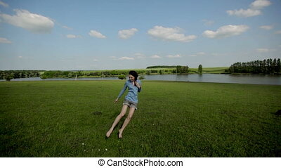 Happy girl running barefoot on green grass