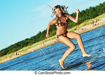 Happy girl running in the sea
