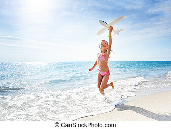Happy girl runs at the beach and holds toy plane