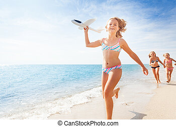 Happy girl runs with airplane model on the beach
