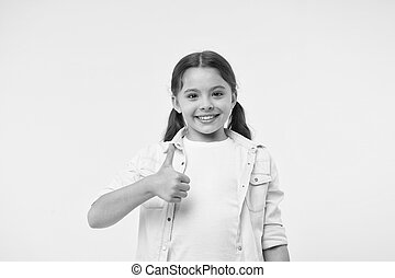 Happy girl show thumbs up on yellow background. Little child smile with hand gesture. Casual look. Beauty and fashion. I like this
