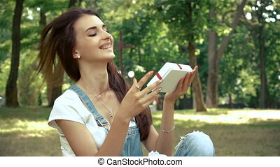 happy girl sits in the Park on the grass and holding gift box
