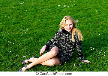 Happy girl sits on a blooming spring meadow in the early morning