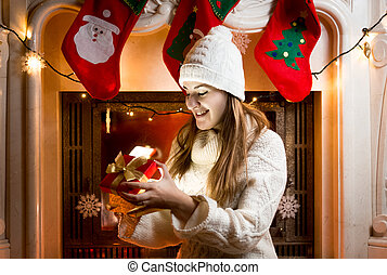 girl sitting at fireplace and looking at gift in box