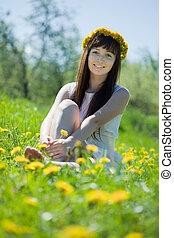 Happy girl sitting in dandelion meadow