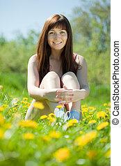 Happy girl sitting in meadow