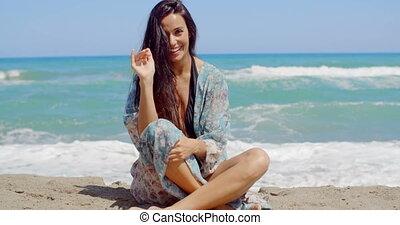 Happy Girl Sitting on Beach Sand Waving her Hand - Happy...