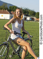 Happy girl sitting on bicycle on the football field