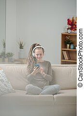Happy girl sitting on couch and scrolling in smartphone while listening to music