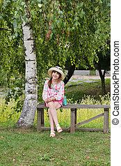 Happy girl sitting on the bench near the birch tree