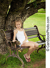 happy girl sitting on the bench near the tree