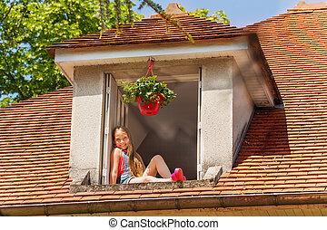 Happy girl sitting on the ledge of attic window