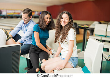 Happy Girl Sitting While Friends Preparing For Bowling