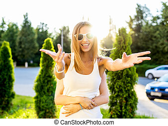 Happy girl smiling bright sunny summer day on street fooled arms to the side and top