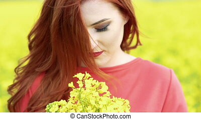 Happy girl smiling on camera with bouquet of rape blossom. Slow motion