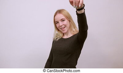 Young Blonde Woman In Black Sweater With Stylish Watch On White Background, Happy Girl Smiling Shows Forefinger Forward. The Concept Of Good, Positive, Successful People