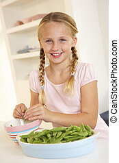 Happy girl splitting peas in kitchen