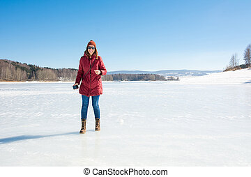 Happy girl standing on a frozen lake