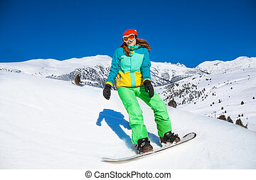 Happy girl standing on snowboard in mountains