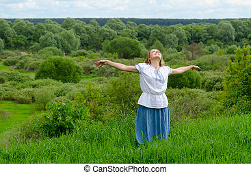 Happy girl stands on background of field with bushes and looks up at sky