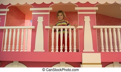 girl stands on second level of children house