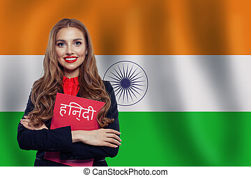 Happy girl student against the India flag background. Book with inscription Hindi on indian language