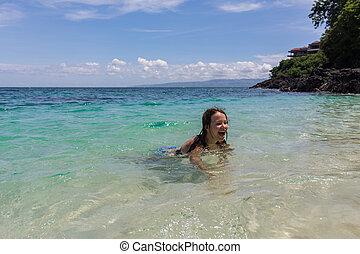 Happy girl swimming in the blue sea