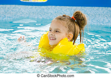 Happy girl swimming in the pool