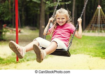 Happy girl swinging on playground